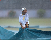 A young Test Match helper doesn't mind the rain, Dhaka, Bangladesh.