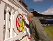 Painting the carved players gates outside the pavilion
