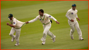 Yasir Hameed is grabbed by Umar Akmal after catching Jonathan Trott.